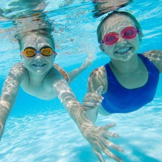 children swimming in a pool with swim molds